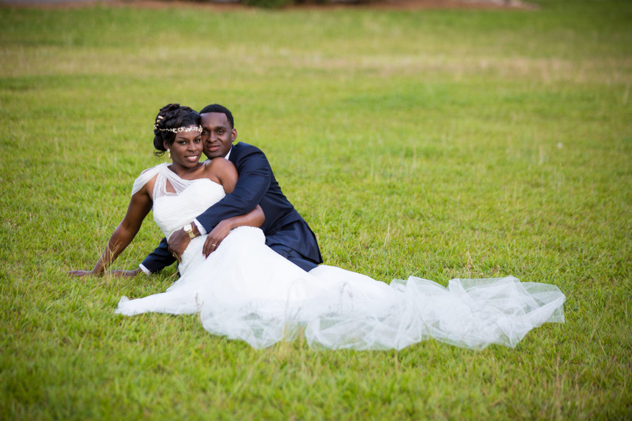 Newly Weds sitting on grass on their Wedding Day